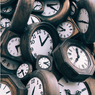 pile of clocks, all telling different times