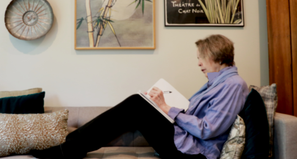 Anne sits on couch, writing in journal