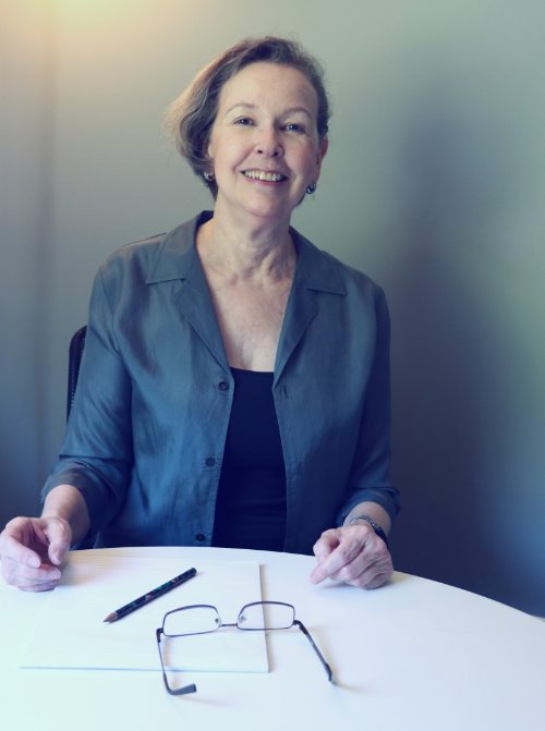 Anne smiles at office table